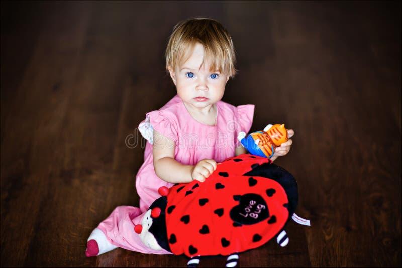 非常坐地板和拿着玩具小伙子的逗人喜爱的小女孩 免版税图库摄影