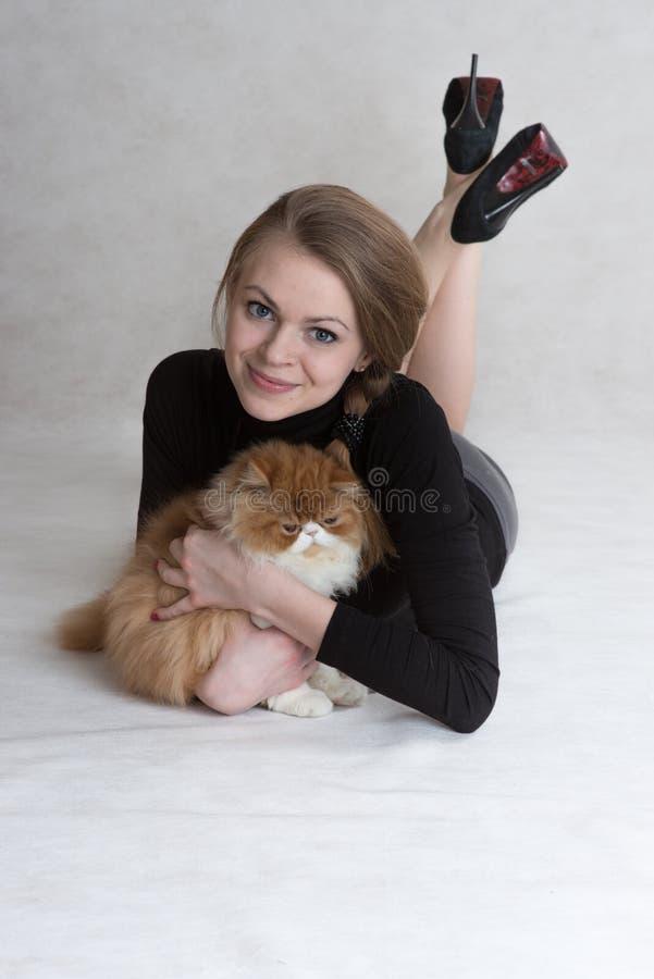 非常好女孩拿着一只红色小猫 库存图片