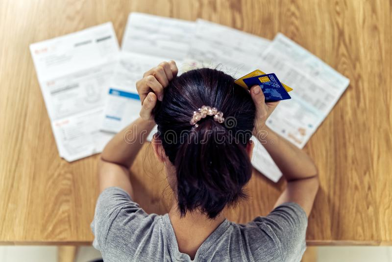 非常强调了举行对发现金钱的年轻坐的亚洲妇女手顶头忧虑支付信用卡债务 免版税库存照片