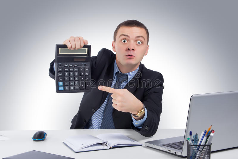 非常恼怒的商人在办公室,拿着计算器 图库摄影