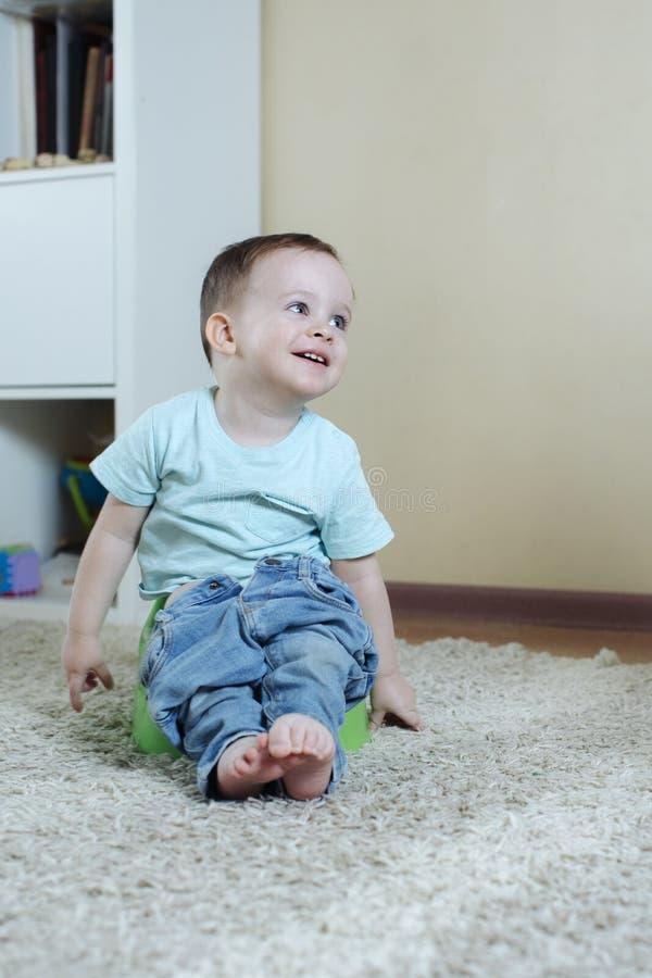 非常愉快和快乐的婴孩坐有下来牛仔裤的罐 免版税库存图片