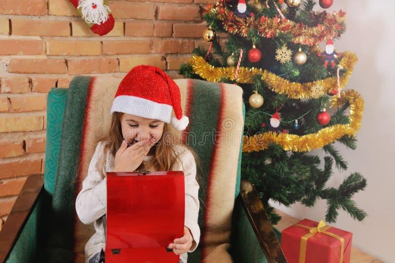 非常有一点红色箱子的逗人喜爱的女婴在椅子的手上在圣诞树附近 免版税库存图片