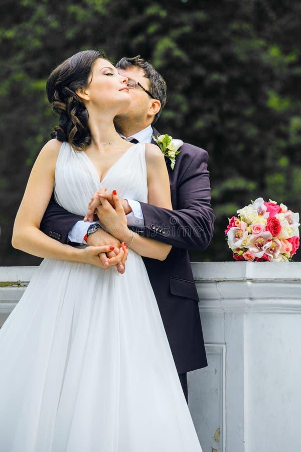 非常有一起拥抱和跳舞在绿色公园,真正婚礼夫妇永远愉快微笑的新郎的美丽的新娘 免版税库存图片