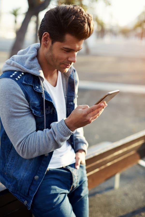 非常有一件时髦的理发和dzhisovoy夹克的性感的年轻英俊的人在手机读消息 库存图片