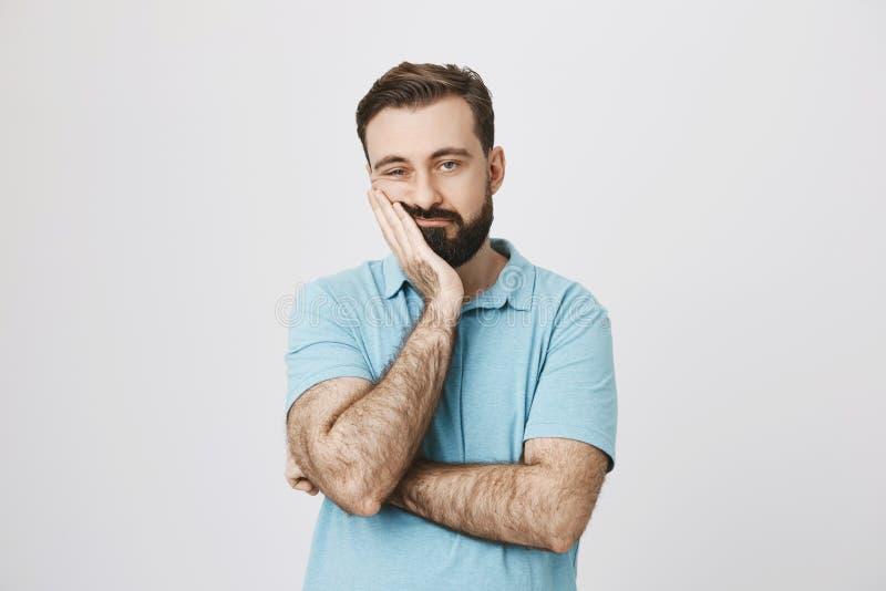 非常有握在面颊的胡子的乏味成人人手,当支持它用另一只横渡的手,看起来疲乏和病态时 库存图片