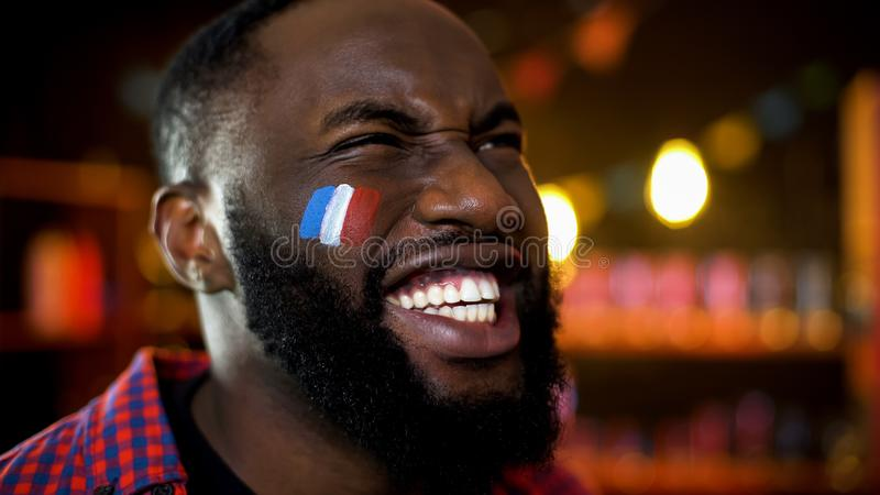 非常有法国旗子的情感黑人爱好者绘在面颊欢呼为队的 库存照片