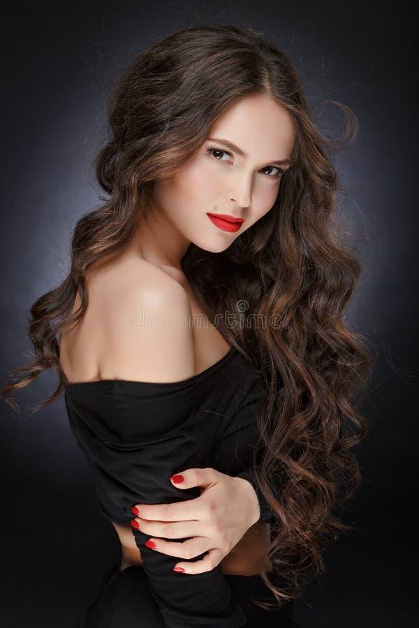非常有长毛绒健康卷发的美丽的魅力女孩在 库存照片
