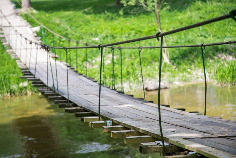 非常横跨河的老垂悬的人行桥 图库摄影