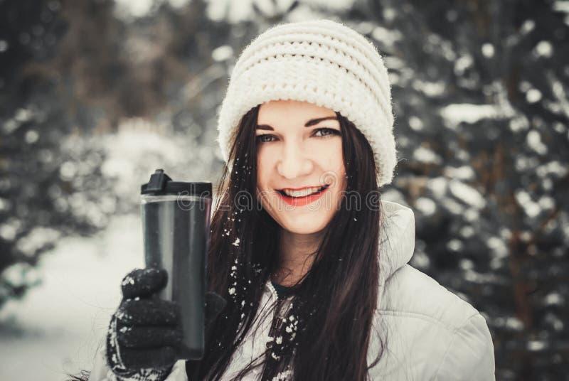 非常正面妇女在冬天公园喝咖啡 纵向冬天妇女年轻人 免版税库存图片