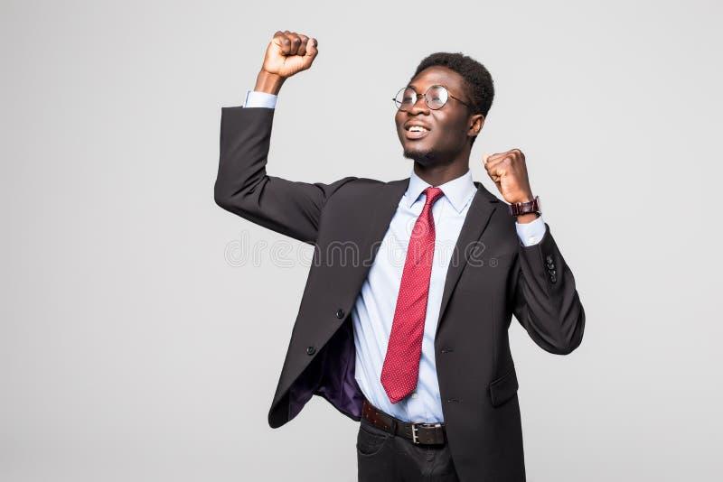 非常激动的非洲商人用被举的手在天空中隔绝了灰色背景 库存照片