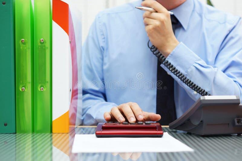 非常电话的繁忙的顾问和工作在有a的计算器 库存图片