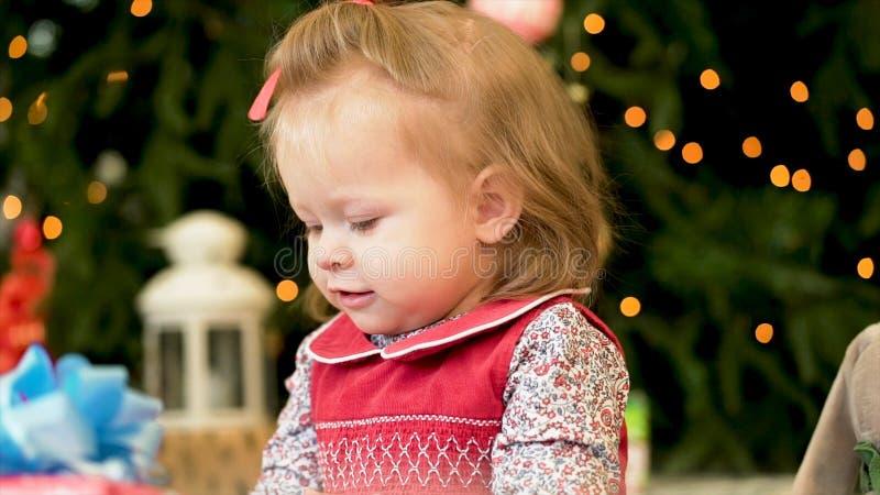 非常红色jaket的好迷人的女孩 使用与在圣诞树背景的玩具的女孩 库存图片