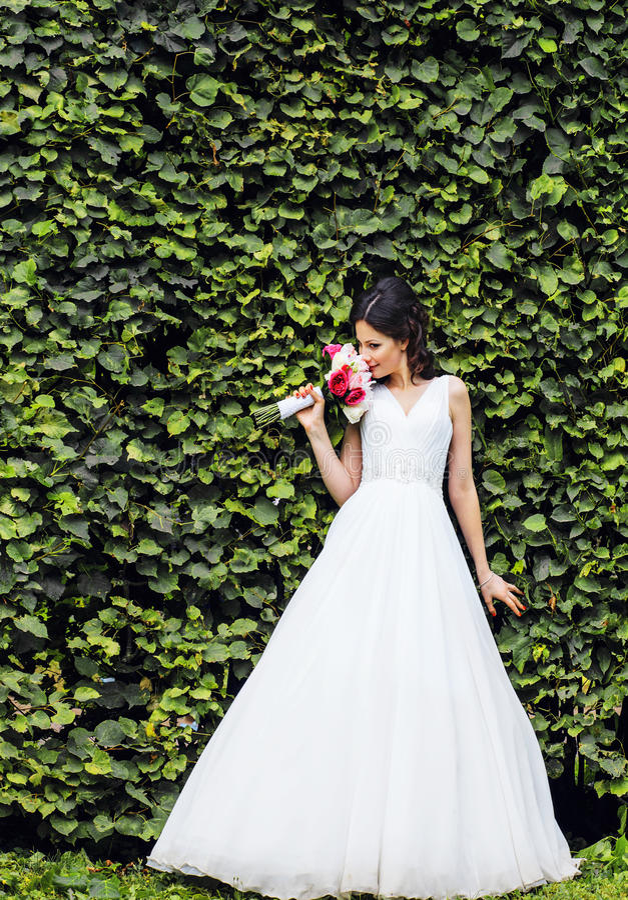 非常美丽的新娘在绿色公园,真正的婚礼愉快微笑, 免版税库存照片