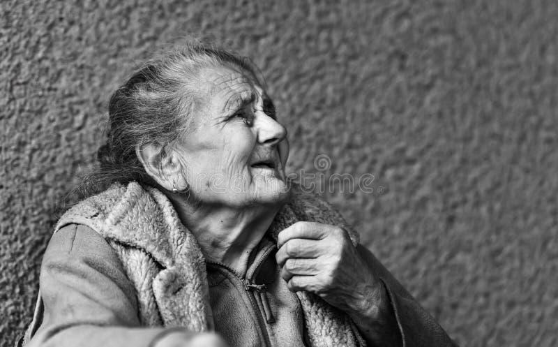 非常老和疲乏的起皱纹的妇女户外 库存照片