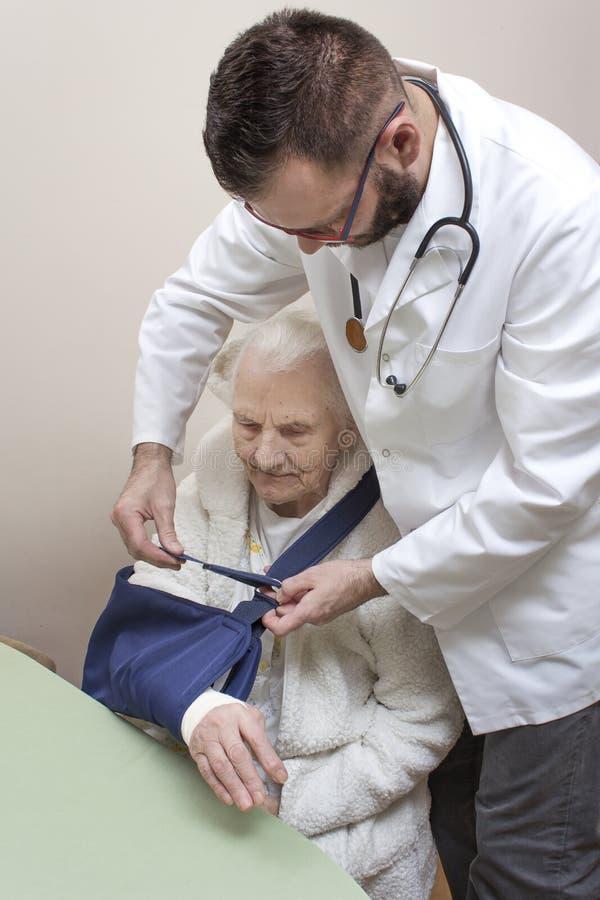 非常老灰发的妇女坐椅子 医生在一个老妇人的胳膊上把吊索放 库存照片