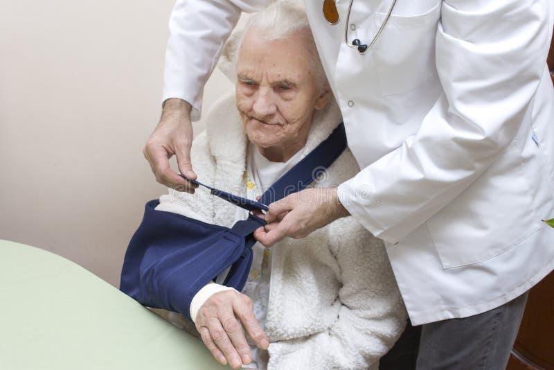 非常老灰发的妇女坐椅子 医生在一个老妇人的胳膊上把吊索放 免版税库存照片