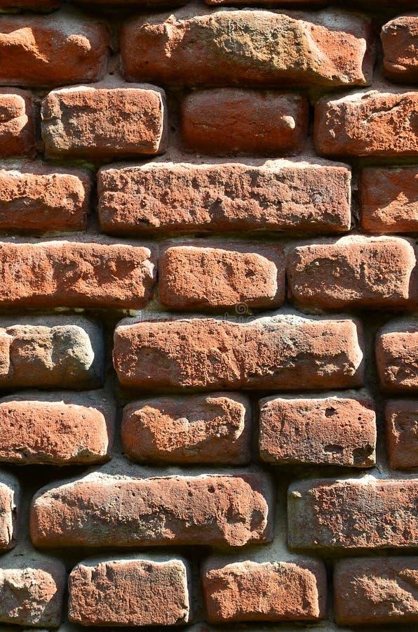 非常老砖砌几行垂直的墙壁纹理由红砖制成 被打碎的和损坏的砖墙用捏的玉米 免版税库存照片