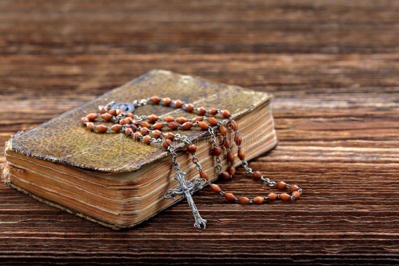 非常老祈祷书和葡萄酒念珠在木背景 免版税库存照片