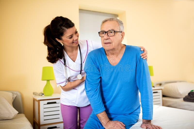 非常耐心护士帮助老老人从床站起来 免版税库存图片