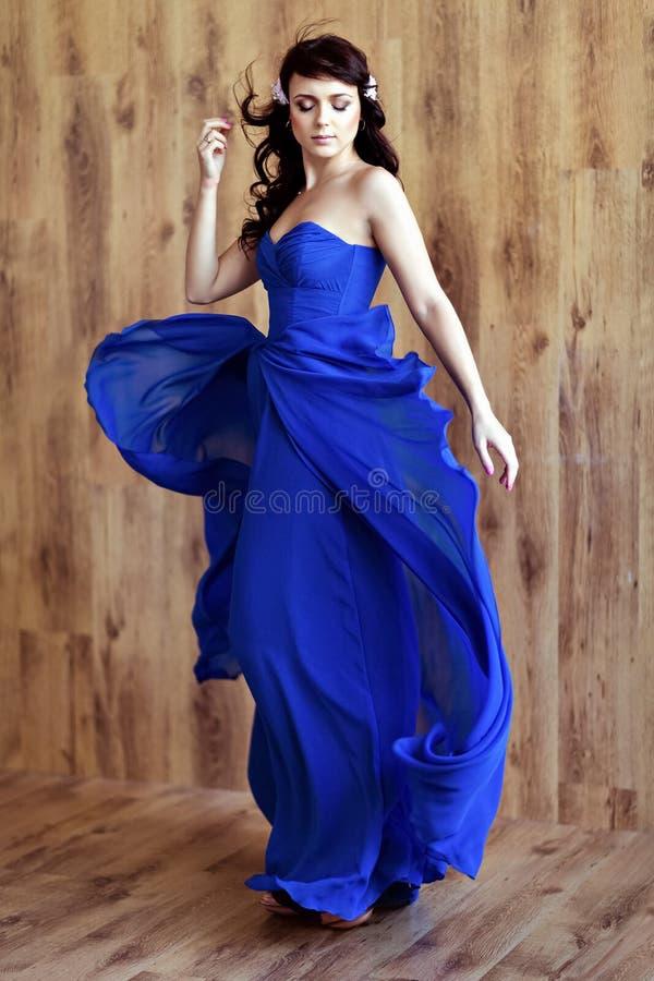 非常蓝色流动的礼服的逗人喜爱的肉欲的美丽的女孩浅黑肤色的男人 免版税库存照片