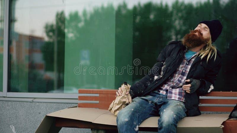 非常醉酒的无家可归的人谈话与走在他附近的人和为金钱乞求,当坐长凳在边路时 库存图片