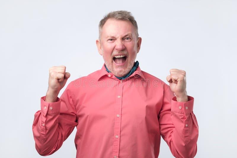 非常高兴的老人赢得,打手势与拳头 免版税库存照片