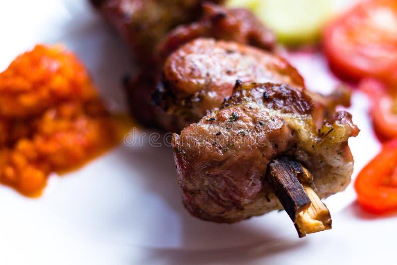 非常鲜美肉块在串被种植并且油煎在开火 肉在一块白色板材说谎 免版税库存照片