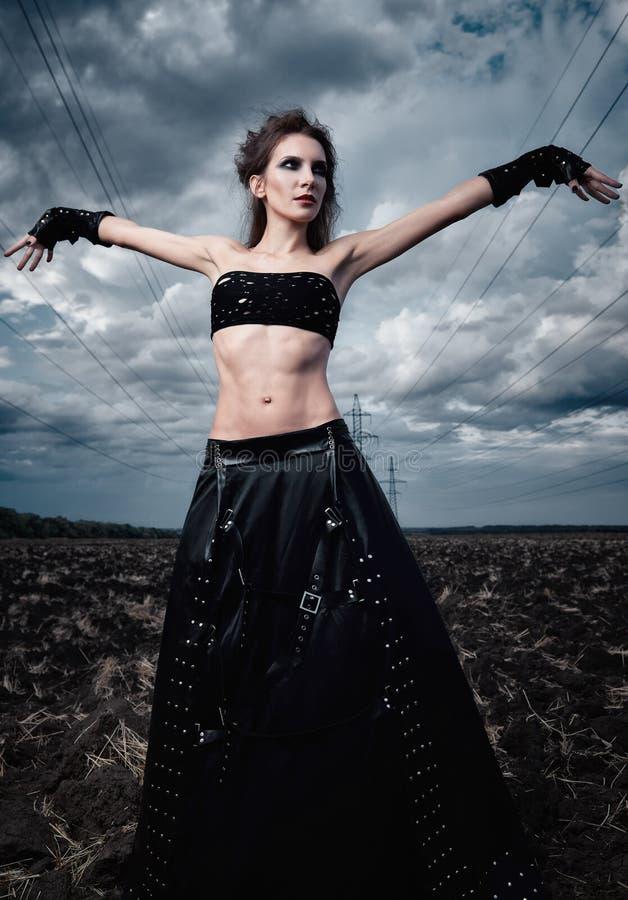 非正式时尚:身着黑色皮裙和手套的漂亮细长哥特式少女 近场户外肖像 图库摄影