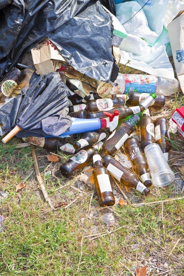 非法倾销与被放弃的瓶、箱子和塑料袋本质上 免版税库存图片
