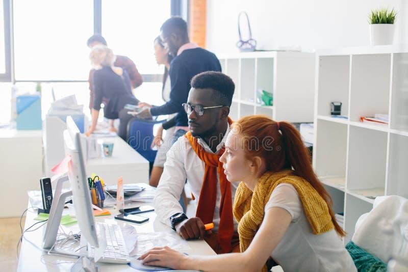 非洲办公室经理和suitting在计算机前面的姜秘书 免版税库存图片