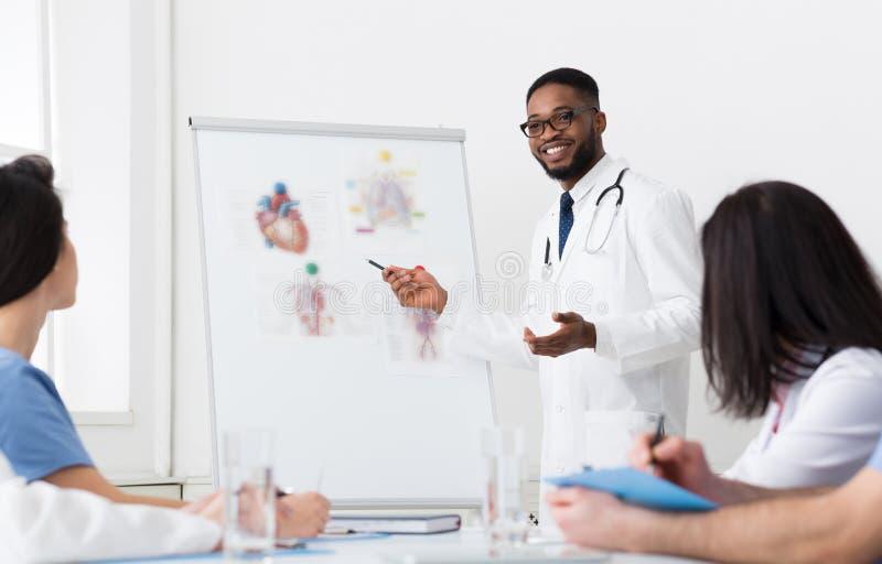 非洲医生Giving Lecture使用Whiteboard的For Colleagues 库存照片