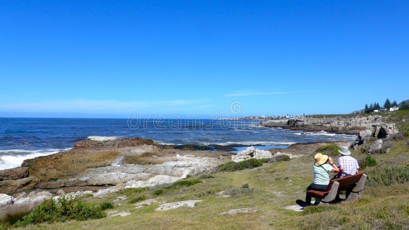非洲南的hermanus 一对年长夫妇坐沿峭壁道路的许多长凳之一并且享受看法 免版税库存图片
