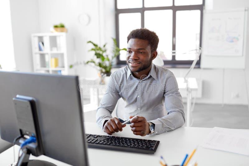 非洲商人与计算机一起使用在办公室 库存照片