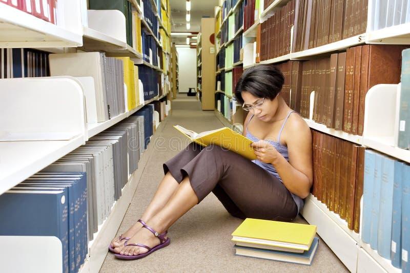 非洲女孩读书坐楼层 库存图片