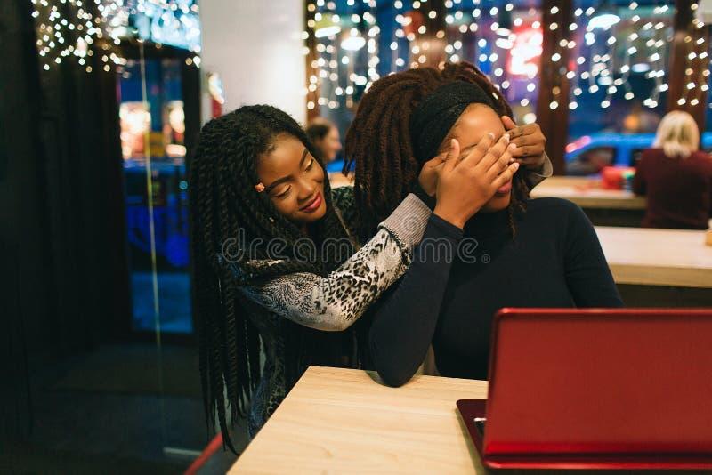 非洲妇女在她的朋友后坐并且保持她的眼睛闭上 第二年轻女人是在与那里红色latop的桌上 库存照片