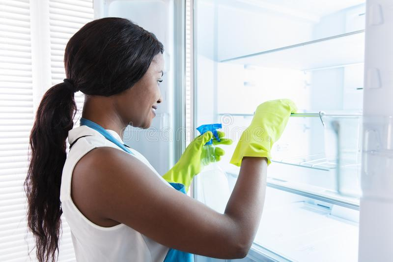 非洲妇女清洁冰箱 免版税库存图片