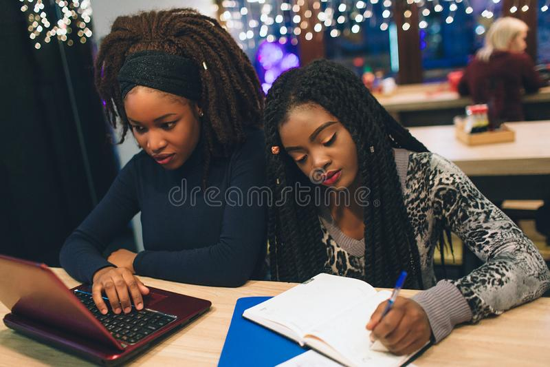非洲年轻女人坐在桌上 在膝上型计算机键盘的第一个类型 第二白色在纸 库存照片