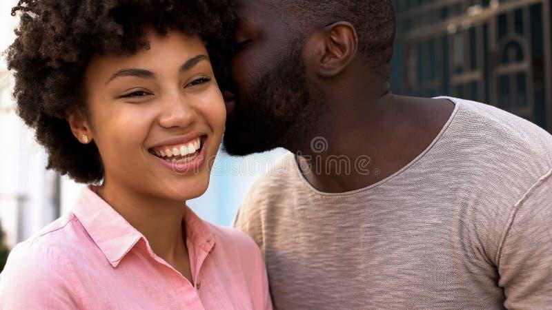 非洲爱的男朋友耳语的词对女朋友,愉快的微笑的夫妇的 免版税库存图片