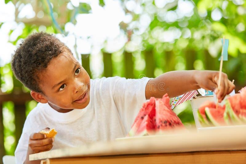 非洲男孩啃西瓜 库存照片