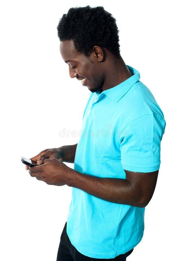 非洲男孩繁忙的传讯 库存照片