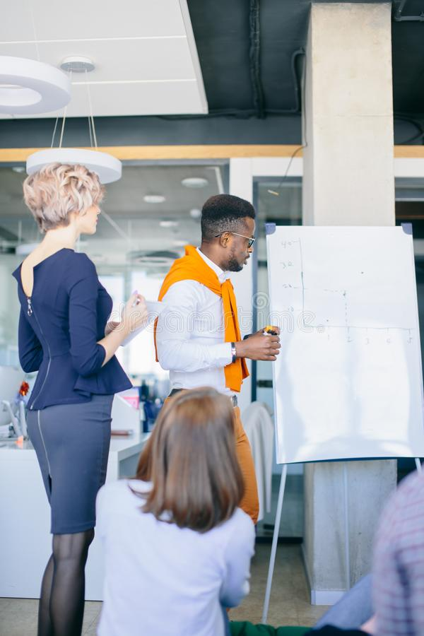非洲男性文字某事在whiteboard 免版税图库摄影