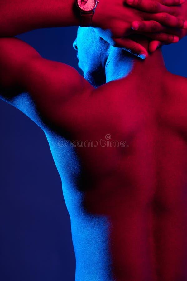 非洲男性运动员背面图有摆在对黑暗的墙壁的赤裸后面的 免版税图库摄影