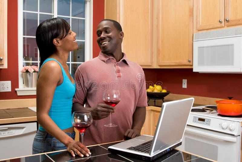 非洲裔美国人的夫妇厨房膝上型计算机使用 库存图片