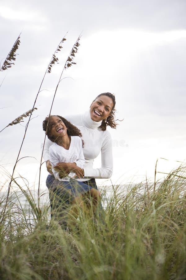 非洲裔美国人的海滩女儿笑的母亲 图库摄影