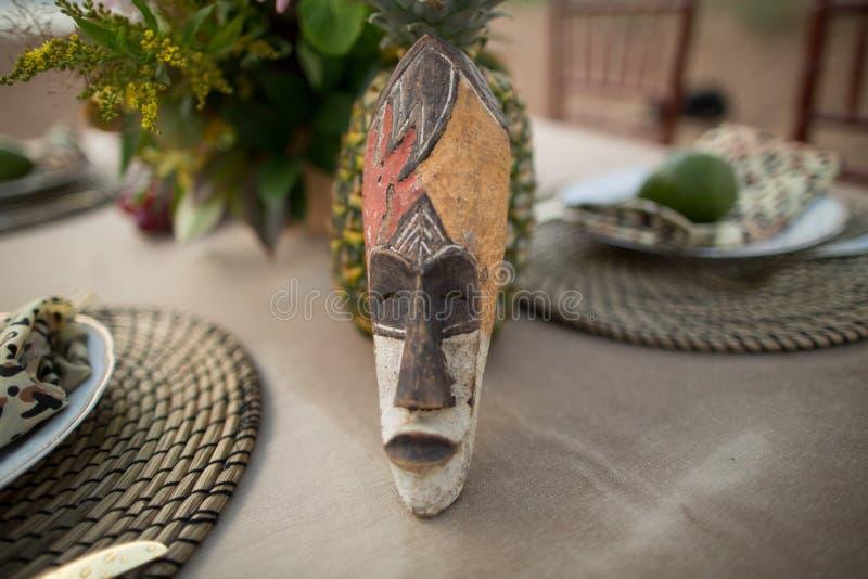 非洲面具安置在一个美妙的桌设置在非洲样式 免版税库存图片