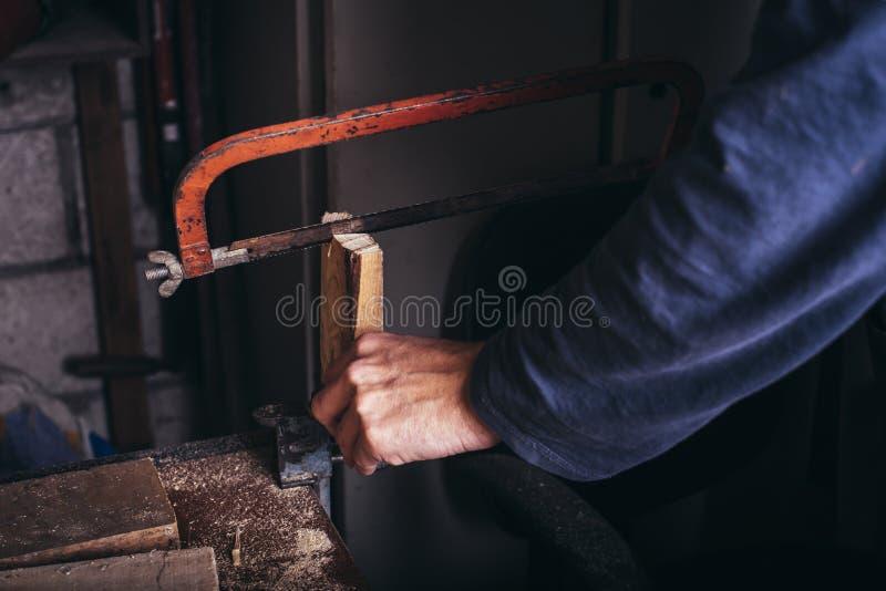 非职业木匠使用手看见了 免版税库存图片