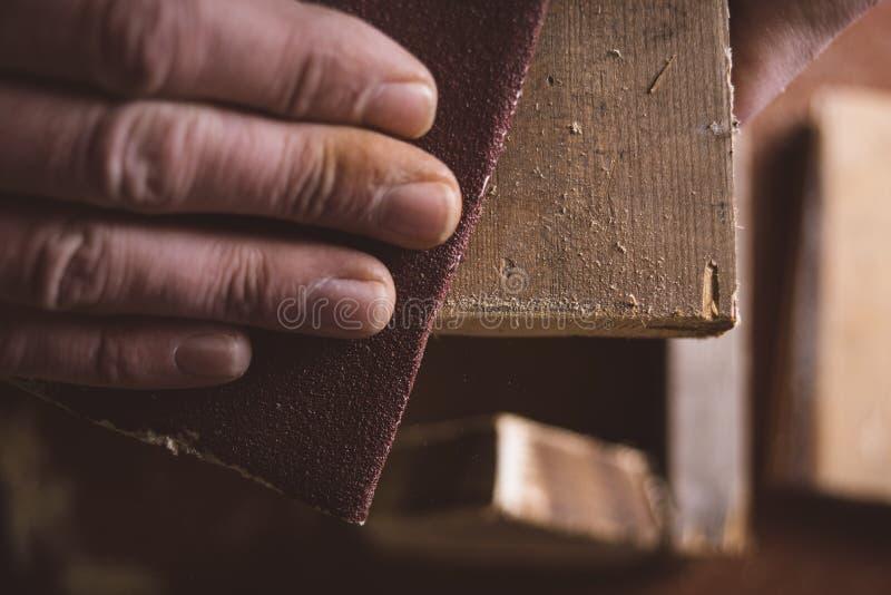 非职业木匠使用铺沙的纸 免版税库存照片