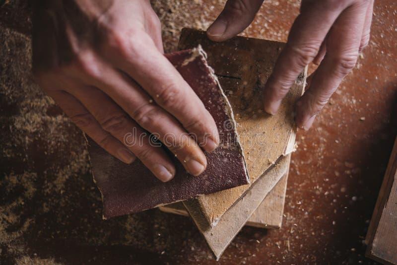 非职业木匠使用铺沙的纸 库存照片