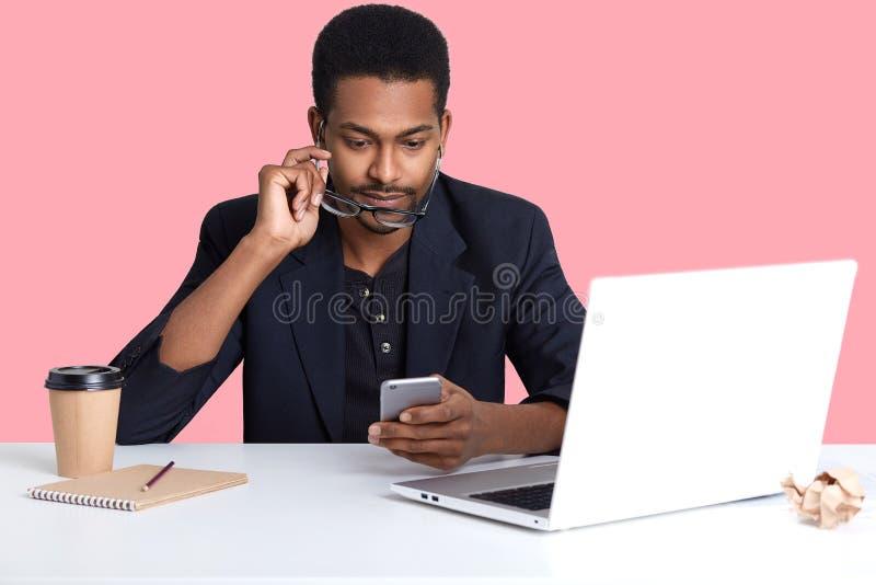 非裔美国人商人接近的画象检查了在他的智能手机的电子邮件,在膝上型计算机前面坐,在网上运转,有 库存照片
