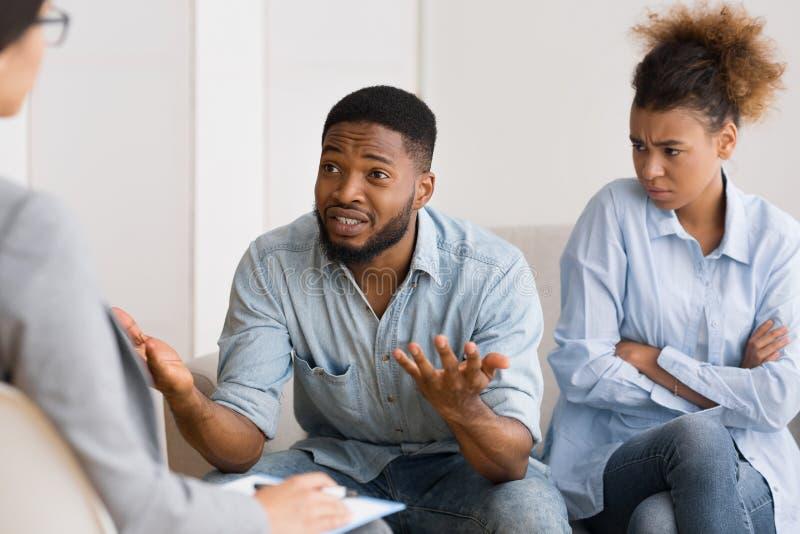 非裔美国人的丈夫谈话与坐在妻子旁边的心理学家 免版税库存照片